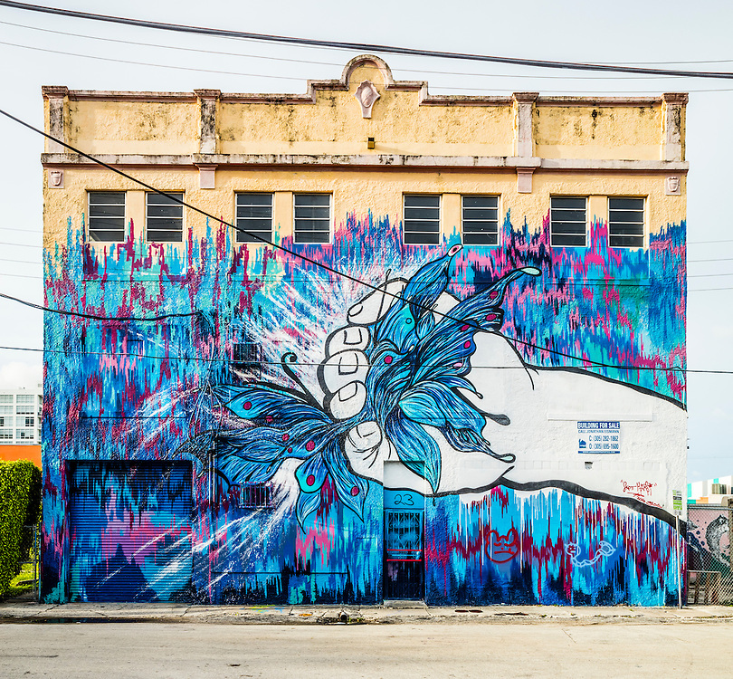 A giant mural covers most of a three-story building in Miami's Wynwood arts district