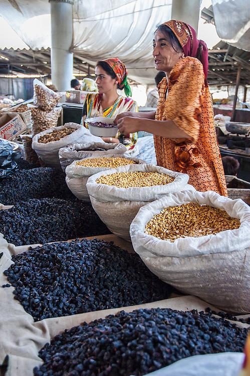 Portrait of a Tajik woman selling raisins and lentils in a market in western Tajikistan
