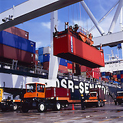 "Import containerized freight is offloaded from a container ship and onto waiting trailer trucks at a seaport dock. - To license this image, click on the shopping cart below - -- Determine pricing and license this image, simply by clicking ""Add To Cart"" below --"