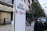 Social disancing sign as Londoners await the imminent second coronavirus lockdown it's business as usual in the West End with large numbers of people, some wearing face masks and some not, coming to Oxford Street to go shopping on what will be the last weekend before a month-long total lockdown in the UK on 1st November 2020 in London, United Kingdom. The three tier system in the UK has not worked sufficiently, to suppress the virus, and there have have been calls by politicians for a 'circuit breaker' complete lockdown to be announced to help the growing spread of the Covid-19.