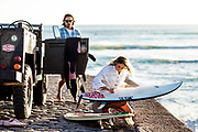 Couple getting ready to go surfing - the woman waxing her surfboard next to their landrover parked on the slipway at St Ouen's Bay Jersey.