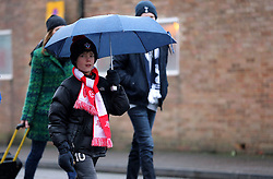 A young Southampton fan shelters from the weather under an umbrella