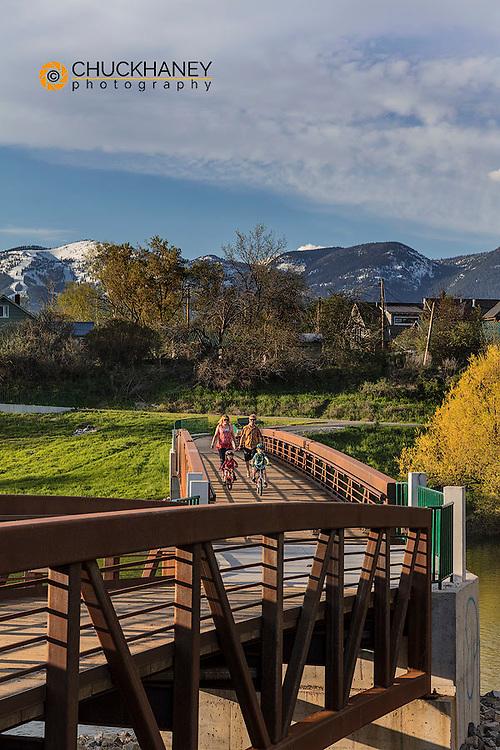 Family traverses bridge over the Whitefish River in Whitefish, Montana, USA MR