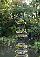 The moss covered Kaisekito Pagoda next to the Midoritaki Waterfall in the Kenrokuen Garden, Kanazawa, Ishigawa, Japan
