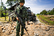 11 JULY 2013 - RAMAN, YALA, THAILAND: A Thai soldier walks away from the scene of an IED attack against members of his unit Thursday. Eight soldiers were injured when the IED exploded under a Thai Army truck carrying soldiers back to their camp after they finished a teacher protection mision. The army routinely dispatches soldiers to protect teachers and Buddhist monks, who have been targeted by Muslim insurgents as representatives of the Bangkok government. More than 5,000 people have been killed and over 9,000 hurt in more than 11,000 incidents in Thailand's three southernmost provinces and four districts of Songkhla since the insurgent violence erupted in January 2004, according to Deep South Watch, an independent research organization that monitors violence in Thailand's deep south region that borders Malaysia.    PHOTO BY JACK KURTZ