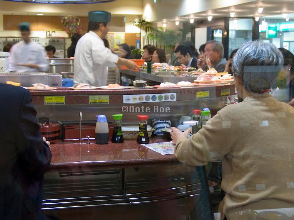 kaiten zushi bar Tokyo counter in sushi bar where sushi is served on conveyor belt