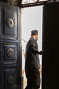 Rear view of priest standing in door at Monastery of Agios Menas, Neohori, Chios, Greece