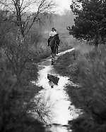 Two horse riders on a morning ride approach a muddy puddle. Photograph by Andrew Tobin/Tobinators Ltd