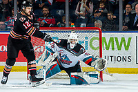 KELOWNA, BC - FEBRUARY 17: Mark Kastelic #12 of the Calgary Hitmen takes a swing at the puck with is stick as Roman Basran #30 of the Kelowna Rockets makes a third period glove save at Prospera Place on February 17, 2020 in Kelowna, Canada. (Photo by Marissa Baecker/Shoot the Breeze)
