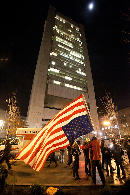 Boston, MA 12/08/2011.An Occupy Boston member stands with the American flag upside down in front of the Federal Reserve building on Thursday evening..Alex Jones / www.alexjonesphoto.com