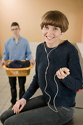 Young woman listening music while man in background, smiling