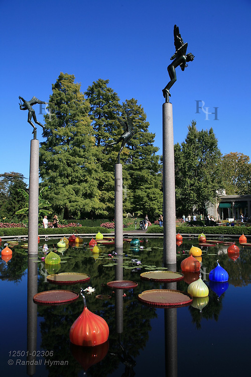 Milles sculpture towers above Chihuly reflecting pond filled with Chihuly glass onion bulbs at Missouri Botanical Garden; St. Louis, Missouri.