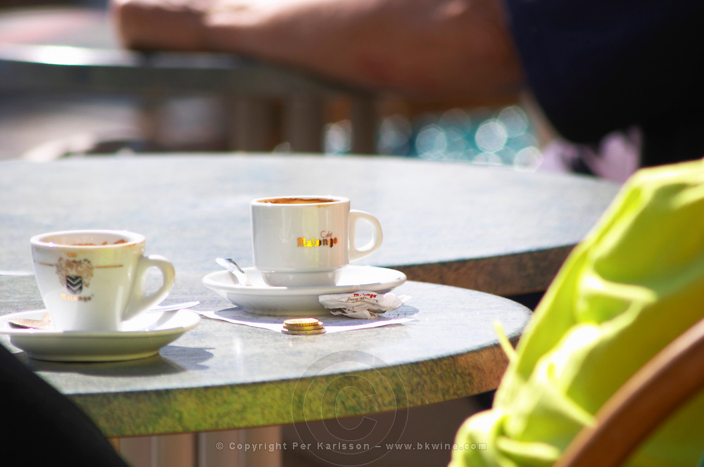 Cafe table with a cup of espresso coffee and a cup of tea and some small change coins on the table Sanary Var Cote d'Azur France