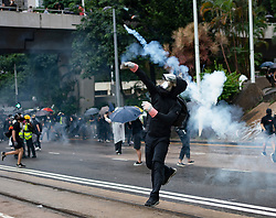 Hong Kong. 6 October 2019. Tens of thousands of pro-democracy protestors march in pouring rain through centre of Hong Kong today from Causeway Bay to Central. Peaceful march later turned violent as a hard-core of protestors confronted police. Pic; Protestor returns a tear gas canister to police. Iain Masterton/Alamy Live News.