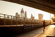 Woman walking under Cannon Street Railway Bridge at sunrise, London, England, UK