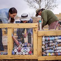 Kari Ballew, left, Bobbi Beckstrom and Hollis Fleischer build an eco-brick wall from recycled bottles and plastic bags outside Double Six Gallery in Grants.