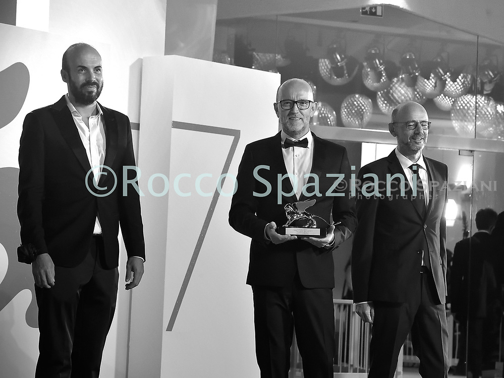 """VENICE, ITALY - SEPTEMBER 12: Davide Romani (C) poses with the Golden Lion for Best Film on behalf of US director Chloe Zhao for """"Nomadland"""" during the winners photocall at the 77th Venice Film Festival on September 12, 2020 in Venice, Italy.<br /> (Photo by Rocco Spaziani)"""