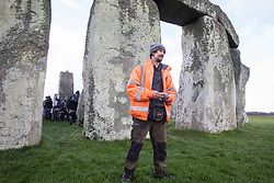Salisbury, UK. 5th December, 2020. Dan Hooper, better known as roads protester Swampy in the 1990s, joins over one hundred people including local residents, climate and land justice activists and pagans at a Mass Trespass at Stonehenge. The trespass was organised in protest against the approval by Transport Secretary Grant Shapps of a £1.7bn project for a two-mile tunnel beneath the World Heritage Site and a further eight miles of dual carriageway for the A303, as well as the government's £27bn Road Investment Strategy 2 (RIS2).