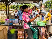 12 FEBRUARY 2015 - BANGKOK, THAILAND:  A Thai iced tea vendor makes an order of Thai iced tea at the new floating market opened along Khlong Phadung Krung Kasem, a 5.5 kilometre long canal dug as a moat around Bangkok in the 1850s. The floating market opened at the north end of the canal near Government House, which is the office of the Prime Minister. The floating market was the idea of Thai Prime Minister General Prayuth Chan-ocha. The market will be open until March 1.   PHOTO BY JACK KURTZ