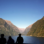Tourists on a cruise ship on Milford Sound, South Island, New Zealand..Milford Sound (Piopiotahi in Ma¯ori) is a fjord in the south west of New Zealand's South Island, within Fiordland National Park and the Te Wahipounamu World Heritage site. It has been judged the world's top travel destination and is acclaimed as New Zealand's most famous tourist destination..Milford Sound runs 15 kilometres inland from the Tasman Sea at Dale Point - the mouth of the fiord - and is surrounded by sheer rock faces that rise 1,200metres (3,900ft) or more on either side. Among the peaks are The Elephant at 1,517metres (4,977ft), said to resemble an elephant's head and The Lion, 1,302metres (4,272ft), in the shape of a crouching lion. Lush rain forests cling precariously to these cliffs, while seals, penguins, and dolphins frequent the waters and whales can be seen sometimes..Milford Sound sports two permanent waterfalls all year round, Lady Bowen Falls and Stirling Falls. After heavy rain many hundreds of temporary waterfalls can be seen running down the steep sided rock faces. .The beauty of this landscape draws thousands of visitors each day, with between 550,000 and 1 million visitors in total per year. This makes the sound one of New Zealand's most-visited tourist spots, and also the most famous New Zealand tourist destination.  Milford Sound, New Zealand. 29th April 2011. Photo Tim Clayton