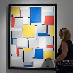 """© Licensed to London News Pictures. 28/06/2018. LONDON, UK. A visitor poses with """"Relational painting No 63"""", 1953, by Fritz Glarner.  Members of the public visit Masterpiece London, the world's leading cross-collecting art fair held in the grounds of the Royal Hospital Chelsea.  The fair brings together 160 international exhibitors presenting works from antiquity to the present day and runs 28 June to 4 July 2018.  Photo credit: Stephen Chung/LNP"""