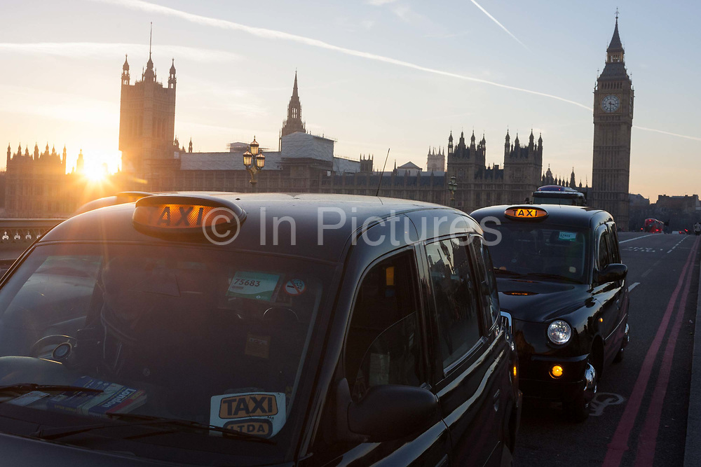 With a setting sun, Big Ben and the Houses of Parliament in the distance, two black London taxies are stopped on Westminster Bridge awaiting a fare, on 30th November 2016, in London, England. Across the brdge, the sun sets behind the Houses of Parliament, currently undergoing major renovation works.