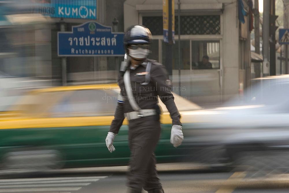 BANGKOK, THAILAND-MARCH 8, 2005:  A traffic policeman directs traffic on the streets of Bangkok, Thailand on March 8, 2005. Photo by David Paul Morris
