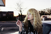 Color portrait of sexy blond girl smoking cigarette leaning on car. Lakewood, NJ 2013