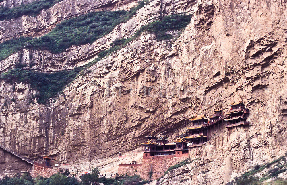 """The """"suspended in the air"""" monastery, correctly known as Xuankong Si, precariously hangs off the Heng Shan mountain range, 65 Kms  south east of Datong city, west of Beijing northern Shanxi province. <br /> This current temple dates back to the 6th century, is comprised of 40 halls of differing sizes, interconnected with narrow walkways or corridors on varying levels. It contain numerous  small shrines with 80 statues of Confucian, Buddhist and Daoist gods in stone, iron, clay and bronze. It attracts vast numbers of Chinese pilgrims and tourists which travel and marvel at its astonishing feat of architectural engineering seen most impressively as you look down into the deep ravine which lies directly below the monastery, apart from its fair share of rain, storms, and earthquakes that have never destroyed this architectural wonder."""