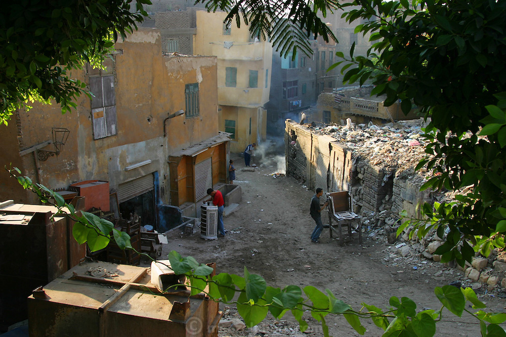 Furniture refinishing in the street outside a small shop in a neighborhood bordering the city of the dead in Cairo, Egypt.