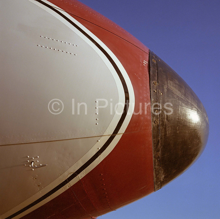 The nose detail of a de Havilland Comet in the colours of the long-defunct airline Dan Air is seen in profile at the Imperial War Museum's Duxford airfield, Cambridgeshire, England. The British de Havilland Comet first flew in July 1949 and is noted as the world's first commercial jet airliner as well as one of the first pressurized commercial aircraft. Early models suffered from catastrophic metal fatigue and the aircraft was redesigned. Here, the nose structure is held together with rivets that sit askew of the aircraft skin making it aerodynamically unfit to fly. It remains however, one of the classic and iconic designs in the history of commercial aviation. Picture from the 'Plane Pictures' project, a celebration of aviation aesthetics and flying culture, 100 years after the Wright brothers first 12 seconds/120 feet powered flight at Kitty Hawk,1903.