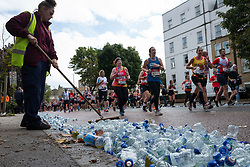 © Licensed to London News Pictures. 03/10/2021. London, UK. A council worker clears discarded water bottles as runners pass through Greenwich as part of the 2021 London Marathon.This London Marathon will be the first full scale staging of the race in more than two years due to the Coronavirus Pandemic.  Photo credit: George Cracknell Wright/LNP