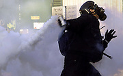 A protestor throws a canister of tear gas back at police during riots outside the Summit of the Americas in Quebec City April 20, 2001. Police have used plenty of tear gas and rubber bullets to quell rioters outside the Summit.  REUTERS/Jim Young