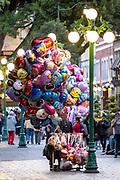 A vendor selling colorful balloons in the central City Square called the Zocalo de Puebla in Puebla, Mexico.