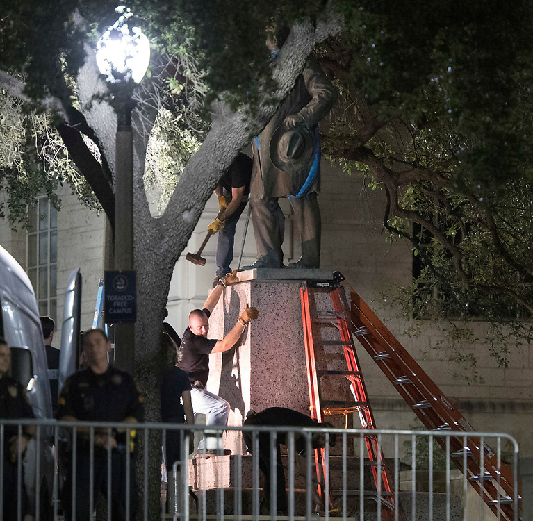 Workers remove the second of four statues of Confederate heroes at the University of Texas in a surprise midnight action before fall classes begin next week. The four are Stephen Hogg, Robert E. Lee, Sidney Johnston and John H. Reagan.