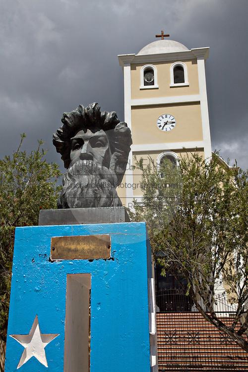 The Monumento a Betances honoring rebel leader Ramon Emeterio Betances in front of the Spanish Colonial style church Iglesia de Parroquia San Jose de la Montana in the Plaza de la Revolucion in Lares, Puerto Rico. Lares is where the 1868 revolt began.