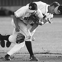 Elks' third baseman Charlie Maxwell, front, and shortstop George Mendazona collide while trying to field a ground ball  during the third inning against Port Angeles at Vince Genna Stadium on Friday.