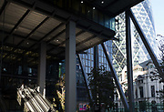 Mid-afternoon sunlight illuminates the escalators of 1, Leadenhall and in the background, the Swiss re Building on St Mary Axe aka The Gherkin in the City of London - the capitals financial district, on 10th October 2018, in London, England.