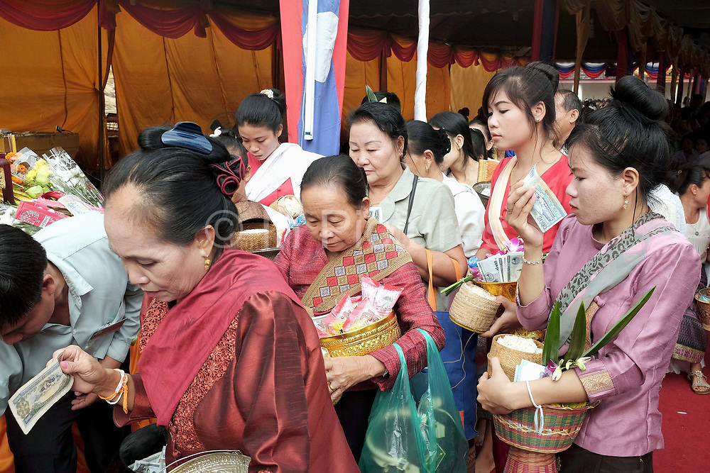 """Alms giving (tak bat) at the That Luang festival, Vientiane, Lao PDR. Pha That Luang is the national symbol and most important religious monument of Laos. Vientiane's most important Theravada Buddhist festival, """"Boun That Luang"""", is held here for three days during the full moon of the twelfth lunar month (November). Monks and laypeople from all over Laos congregate to celebrate the occasion with three days of religious ceremony followed by a week of festivities, day and night. The procession of laypeople begins at Wat Si Muang in the city centre and proceeds to Pha That Luang to make offerings to the monks in order to accumulate merit for rebirth into a better life. The religious part concludes as laypeople, carrying incense and candles as offerings, circumambulate Pha That Luang three times in honor of Buddha."""