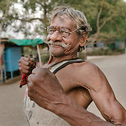 An old man pumps his arms to show his strength.