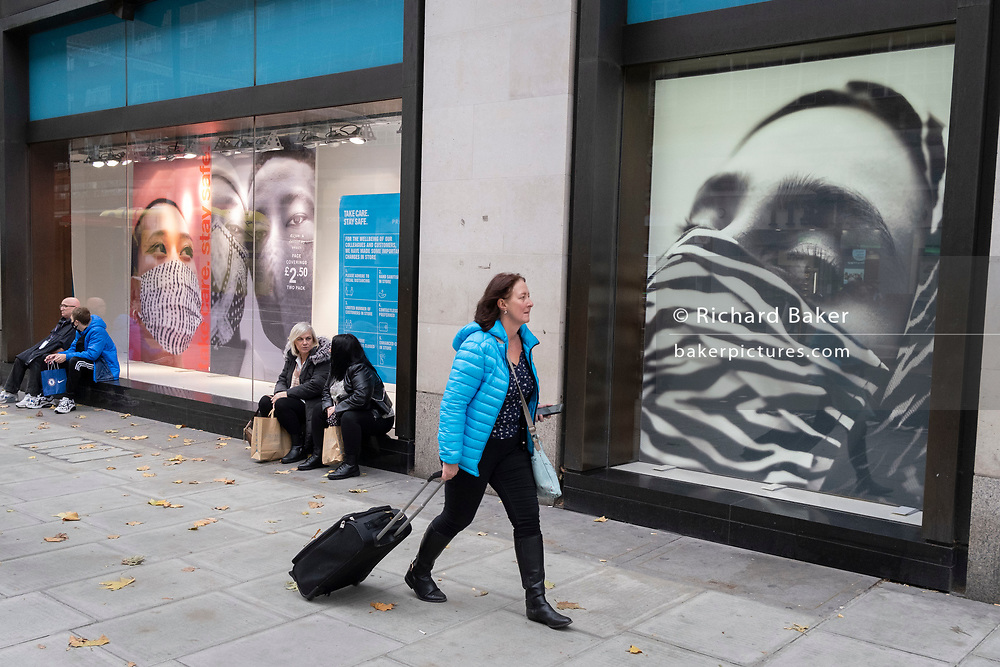 A women walks past a window of Primark that features faces wearing face coverings, sold inside this high street retailer during the second (Autumn) wave of the Coronavirus pandemic, on 30th October 2020, in London, England.