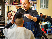 "23 DECEMBER 2017 - HANOI, VIETNAM: A barber gives haircuts in the old quarter of Hanoi. The old quarter is the heart of Hanoi, with narrow streets and lots of small shops but it's being ""gentrified"" because of tourism and some of the shops are being turned into hotels and cafes for tourists and wealthy Vietnamese.      PHOTO BY JACK KURTZ"
