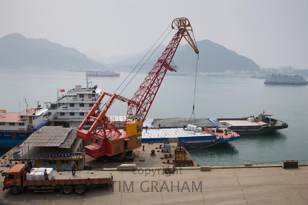 Loading dock crane lifts aluminim ingot blocks onto cargo ship, Yichang, China