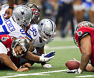 DALLAS, TX - SEPTEMBER 23:  Josh Freeman #5 of the Tampa Bay Buccaneers fumbles the ball against the Dallas Cowboys at Cowboys Stadium on September 23, 2012 in Dallas, Texas.  The Cowboys defeated the Buccaneers 16-10.  (Photo by Wesley Hitt/Getty Images) *** Local Caption *** Josh Freeman Sports photography by Wesley Hitt photography with images from the NFL, NCAA and Arkansas Razorbacks.  Hitt photography in based in Fayetteville, Arkansas where he shoots Commercial Photography, Editorial Photography, Advertising Photography, Stock Photography and People Photography