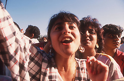Group of teenage girls shouting and waving at music festival,