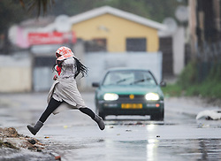 South Africa - Cape Town - 09 July 2020 -  A women jumps over a puddle of water in Wallacedene. A major cold front has made landfall in the Western Cape. Its expected to bring bitterly cold and wet weather, with strong to gale-force north-westerly winds of 60-74km/h and gusts up to 100km/h. The cold front is followed by another cold front and the Western Cape can expect to have cold weather until Sunday.  Picture: Henk Kruger/African News Agency(ANA)
