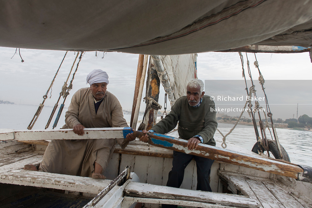 Two crewmen of a felucca row their boat during a drop in wind while sailing on the River Nile at Luxor, Nile Valley, Egypt. Feluccas are ancient Egyptian sail boats which were used in ancient times as a primary mode of transport and are the only type of boat that is still used extensively in the country.