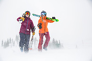 SHOT 3/15/16 12:44:10 PM - Skiiers Hannah Follender<br /> and McKenna Peterson walk to hikable territory at Alta ski area as winds whip up fresh snow. Alta is a ski area in the western United States, located in the town of Alta in the Wasatch Mountains of Utah, in Salt Lake County. With a skiable area of 2,200 acres, Alta's base elevation is 8,530 ft and rises to 10,550 ft for a vertical gain of 2,020 ft. One of the oldest ski resorts in the country, it opened its first lift in early 1939. Alta is known for being very high altitude and receives more snow than most Utah resorts, its average annual snowfall is 514 inches. Alta is one of three remaining ski resorts in America that prohibits snowboarders. (Photo by Marc Piscotty / © 2016)