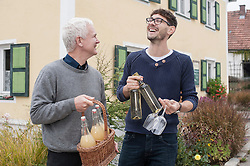 Father and son holding bottles of white wine and apple juices and laughing, Bavaria, Germany