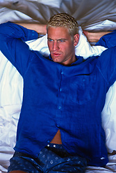 Bleach blond man in a blue shirt and blue boxers resting on a bed